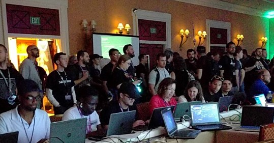 Attendees at a cybersecurity conference with laptops