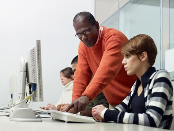 An instructor helping a computer student