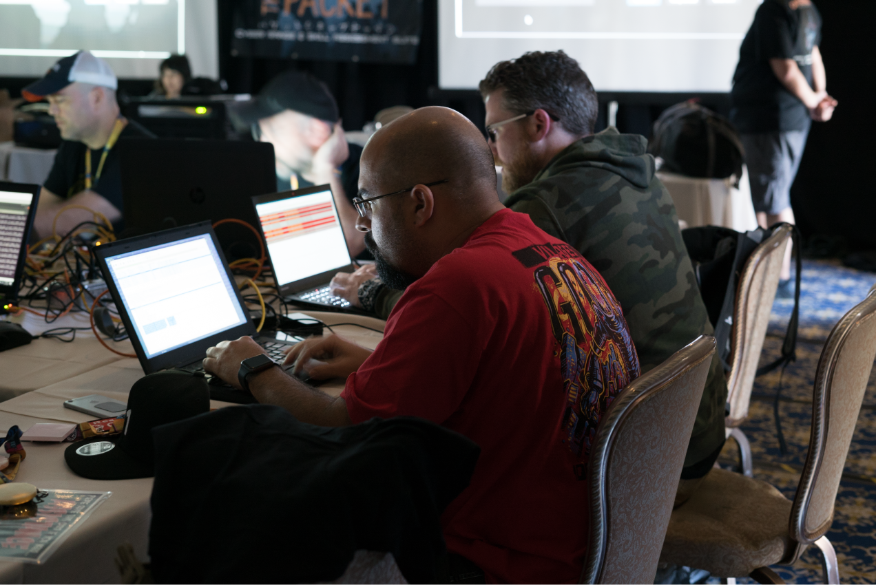 Several hackers at DEF CON using laptops.