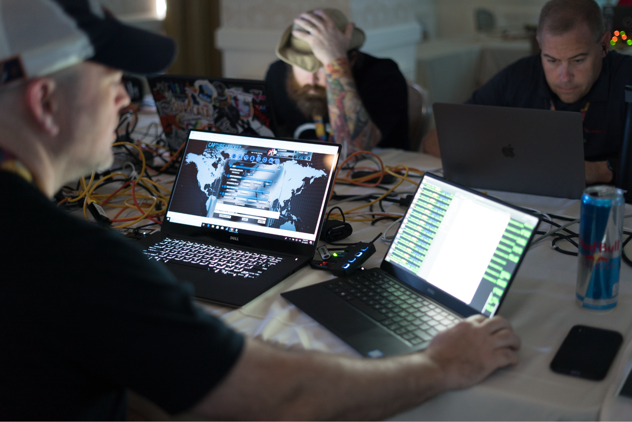 Three hackers sitting at a table together using laptops. Capture The Packet is visible on one screen.