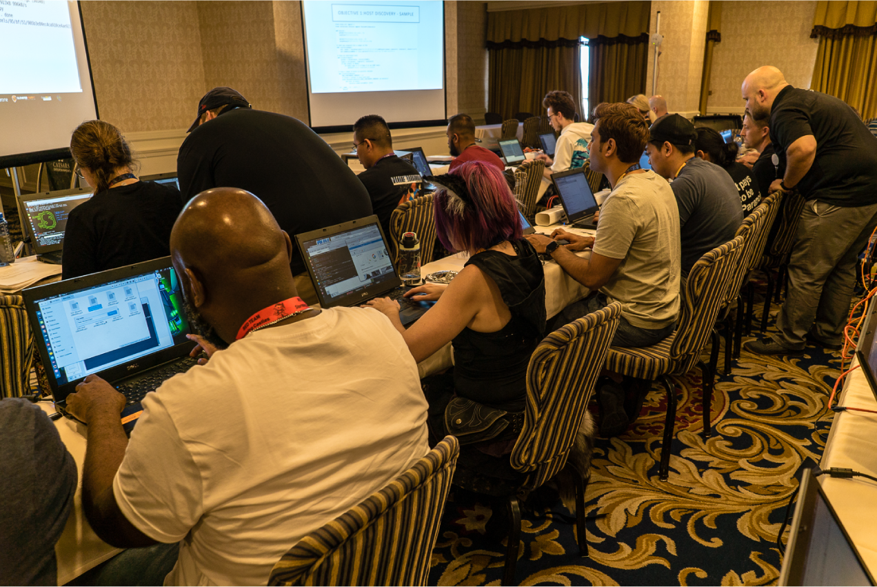 Hackers at DEF CON sitting at long tables with laptops.