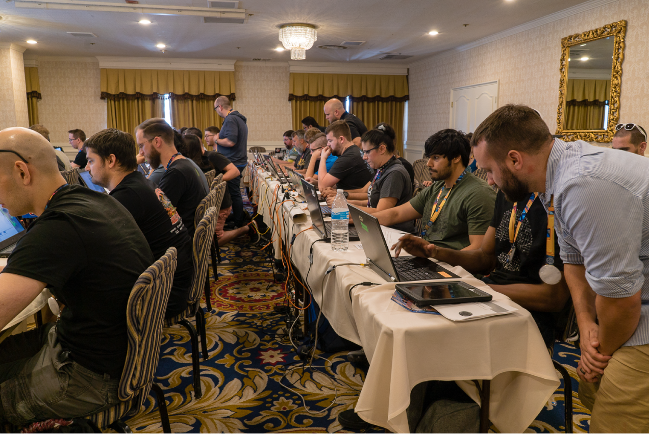 A room full of hackers sitting at long tables using laptops.