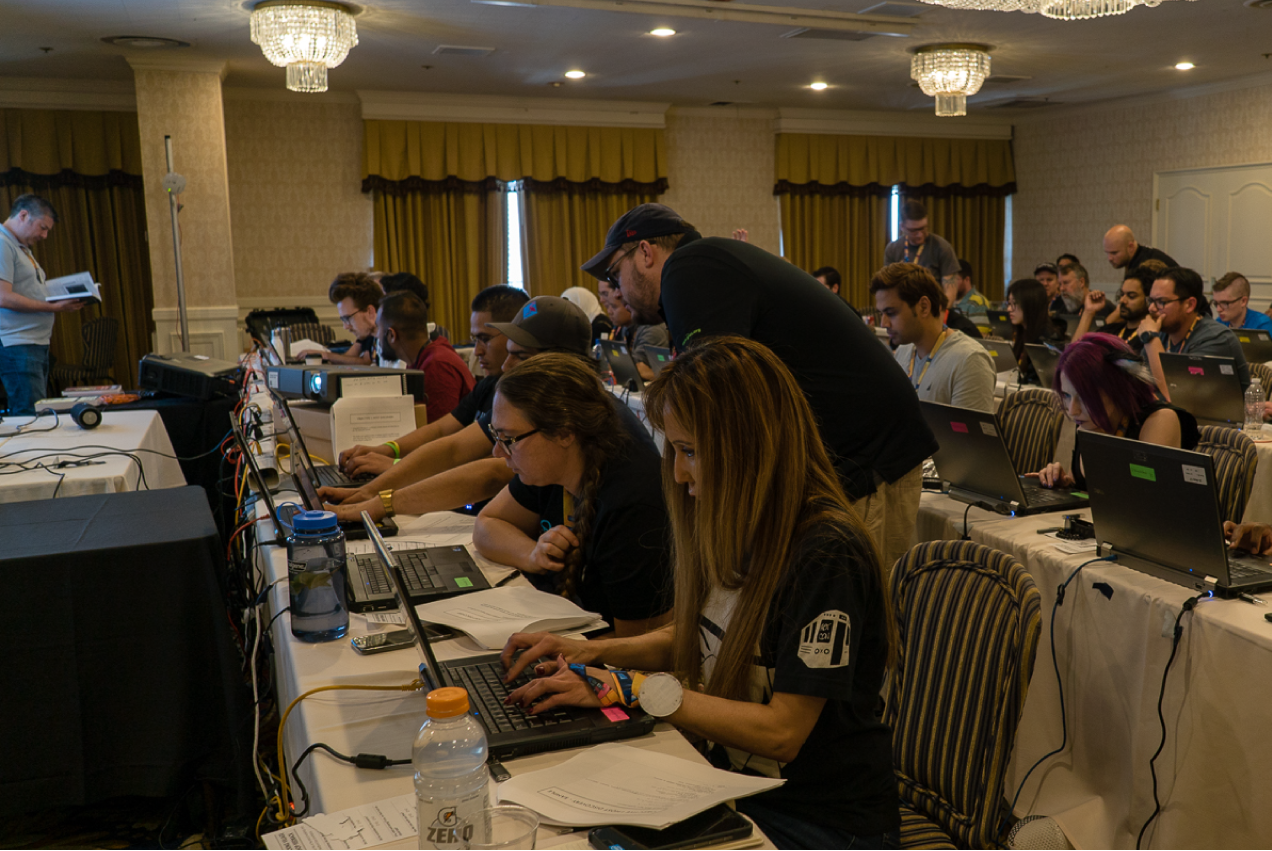 Hackers at long tables working on laptops.