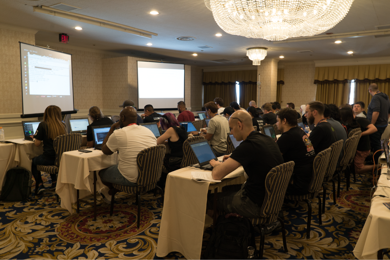 A room of hackers sitting at long tables with laptops.