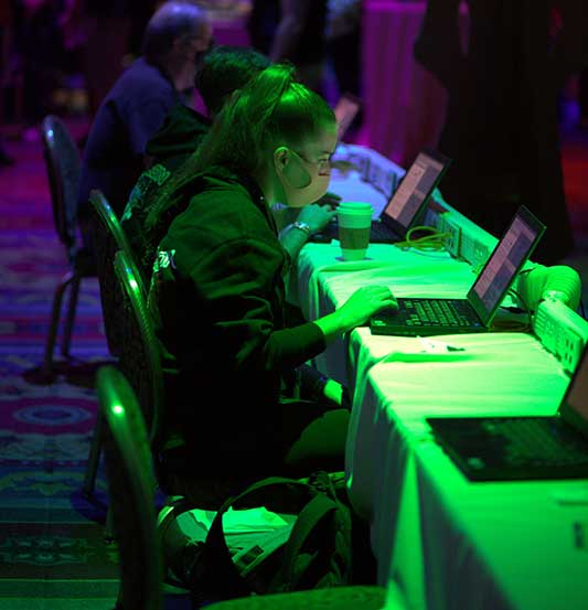 A female hacker wearing a mask sits at a table with others using a laptop at the Packet Hacking Village.